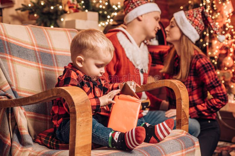 Cheerful cute baby opening a Christmas present. Christmas for happy family. Lovely kissing parents on the background royalty free stock image