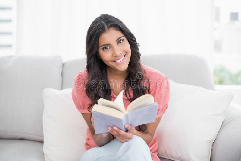 Cheerful cute brunette sitting on couch reading a book stock photo