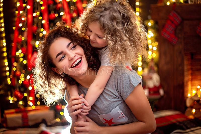 Cheerful cute curly little girl and her older sister having fun, hugging near christmas tree indoors. stock image