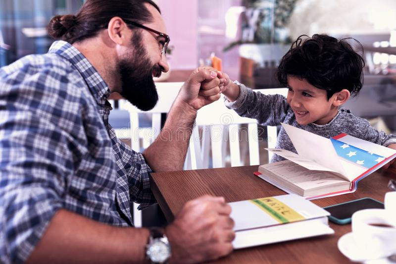 Cheerful cute dark-eyed son feeling amazing having fun with his father stock image