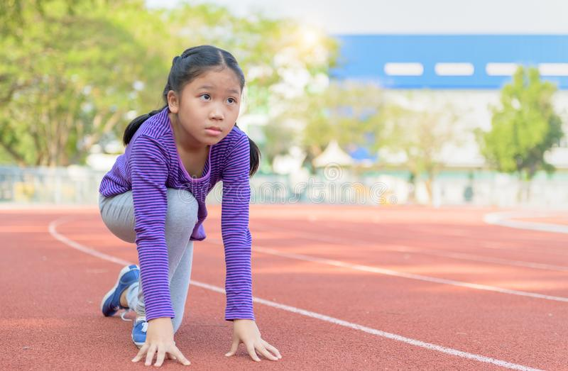 Cheerful cute girl in ready position to run on track royalty free stock photos