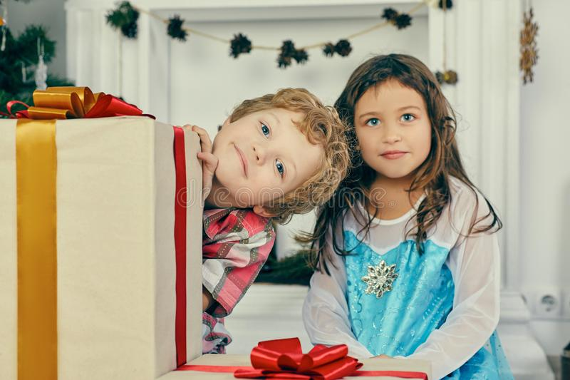 Cheerful cute little childs with presents. Boy and girl holding a gift boxes near Christmas tree indoors. royalty free stock photo