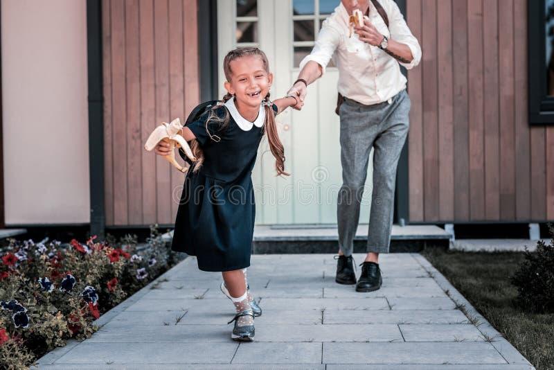 Cheerful cute little schoolgirl holding banana on her way to school. Cheerful schoolgirl. Cheerful cute little schoolgirl holding banana on her way to school stock photo