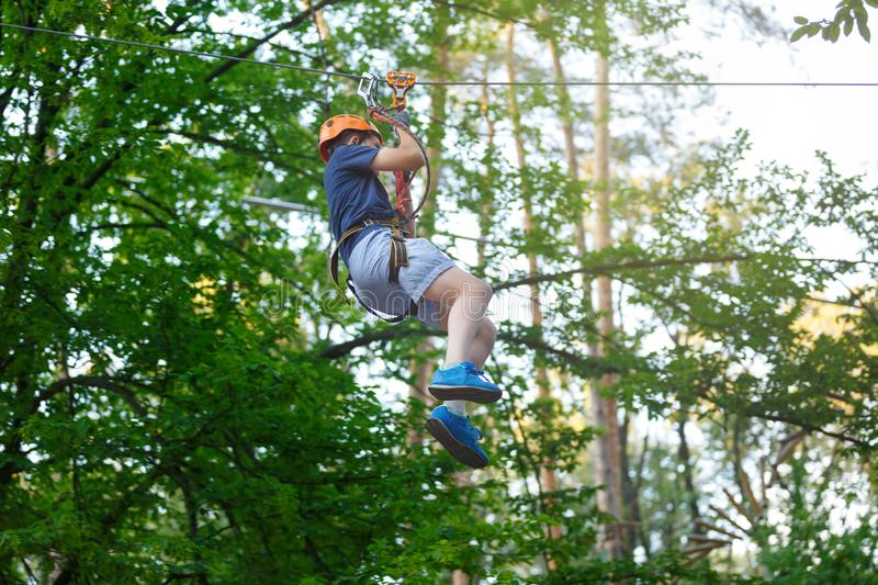 Cheerful cute young boy in blue t shirt and orange helmet in adventure rope park at sunny summer day. Active lifestyle, sport. Holidays for children royalty free stock image