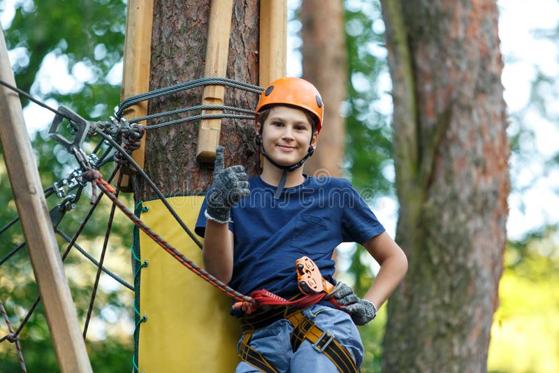 Cheerful cute young boy in blue t shirt and orange helmet in adventure rope park at sunny summer day. Active lifestyle, sport. Holidays for children stock photography