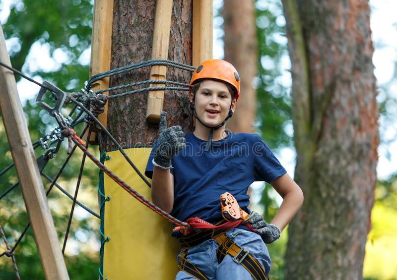 Cheerful cute young boy in blue t shirt and orange helmet in adventure rope park at sunny summer day. Active lifestyle, sport,. Holidays for children stock photos