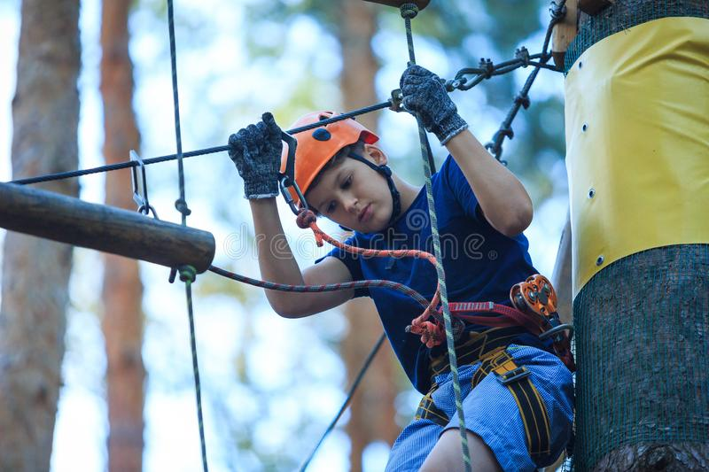 Cheerful cute young boy in blue t shirt and orange helmet in adventure rope park at sunny summer day. Active lifestyle, sport. Holidays for children royalty free stock images