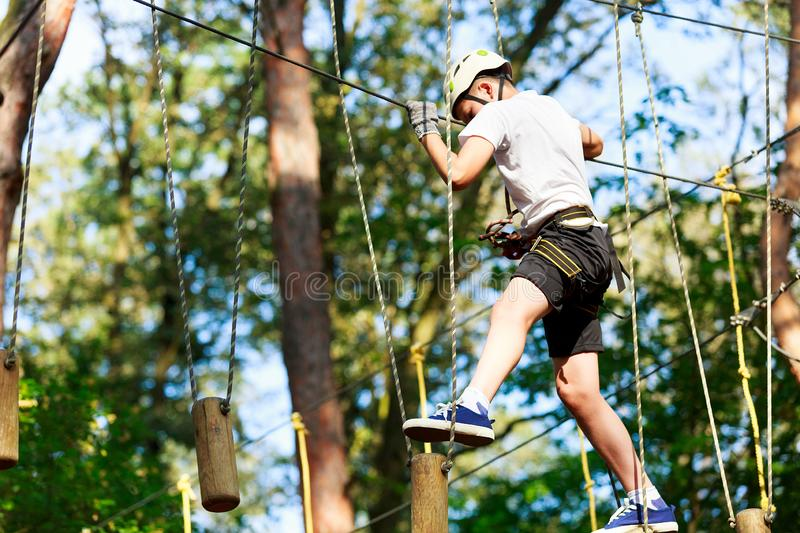 Cheerful cute young boy in white t shirt and white helmet in adventure rope park at sunny summer day. Active lifestyle, sport, royalty free stock images