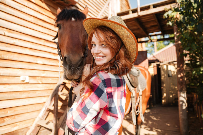 Cheerful cute young woman cowgirl in hat with horse stock images