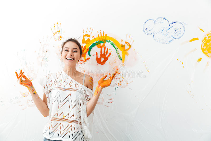 Cheerful cute young woman painting on white wall by hands stock photos