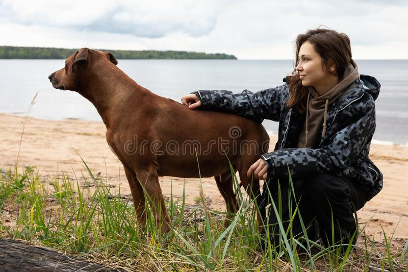 A cheerful cute young woman sits and hugs her dog on the beach. Rhodesian Ridgeback with mistress on the lake. stock photography