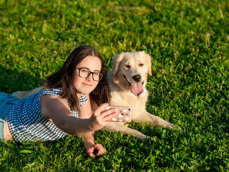 Young woman and her friendly dog taking a selfie at a park royalty free stock images