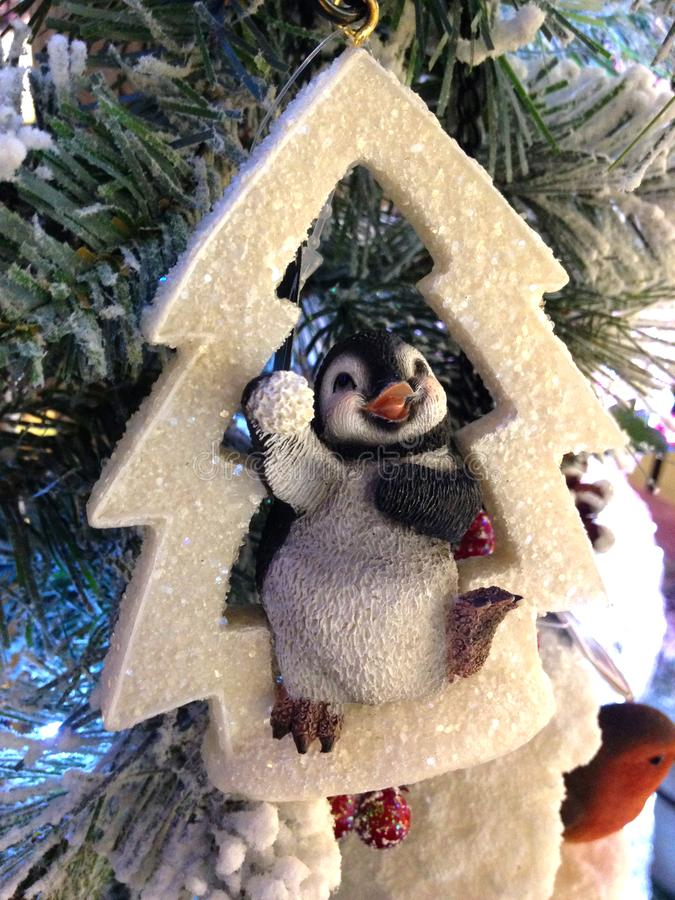 Cheerful Penguin Decoration hanging on white Christmas tree royalty free stock photography