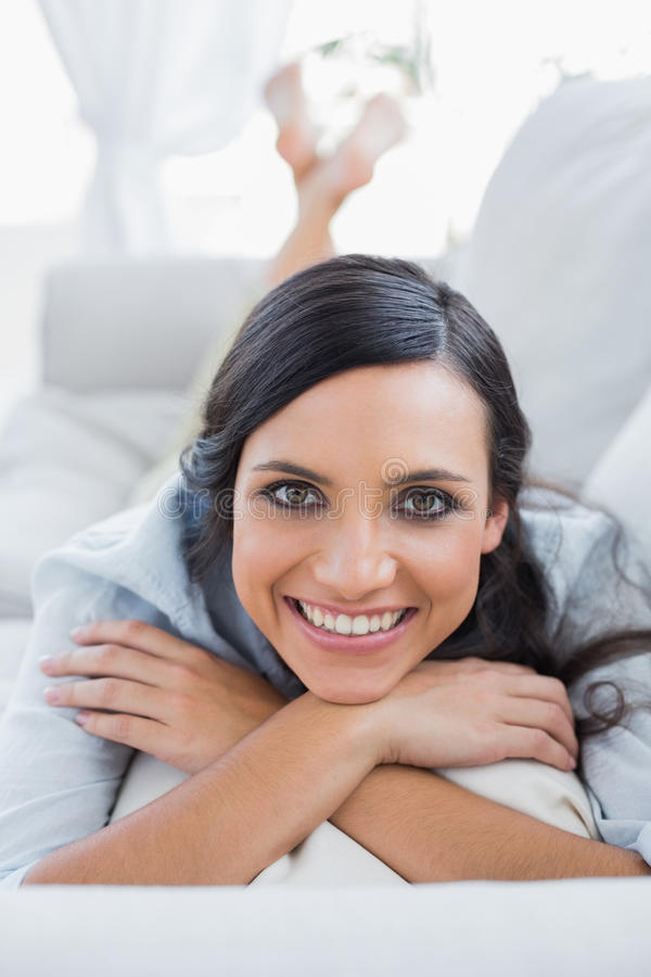 Cheerful dark hair woman lying on the couch royalty free stock photos