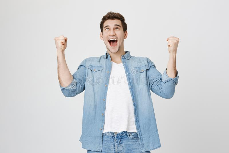 Cheerful dark-haired attractive European unshaven male with opened mouth being excited and glad to achieve victory royalty free stock photography