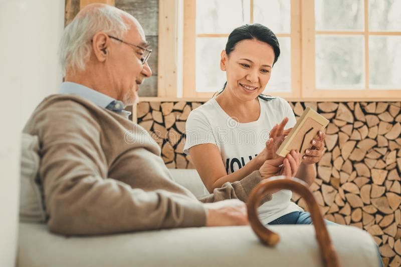 Cheerful dark-haired lady showing photo frame to pensioner. Woman volunteer. Cheerful dark-haired lady showing photo frame to pensioner while they chilling on royalty free stock image