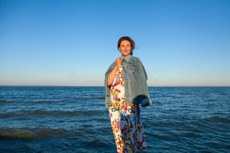 A cheerful dark-haired woman in the colored thread and denim jacket smiles, walks along the beach and enjoys the bright sun on a stock photos