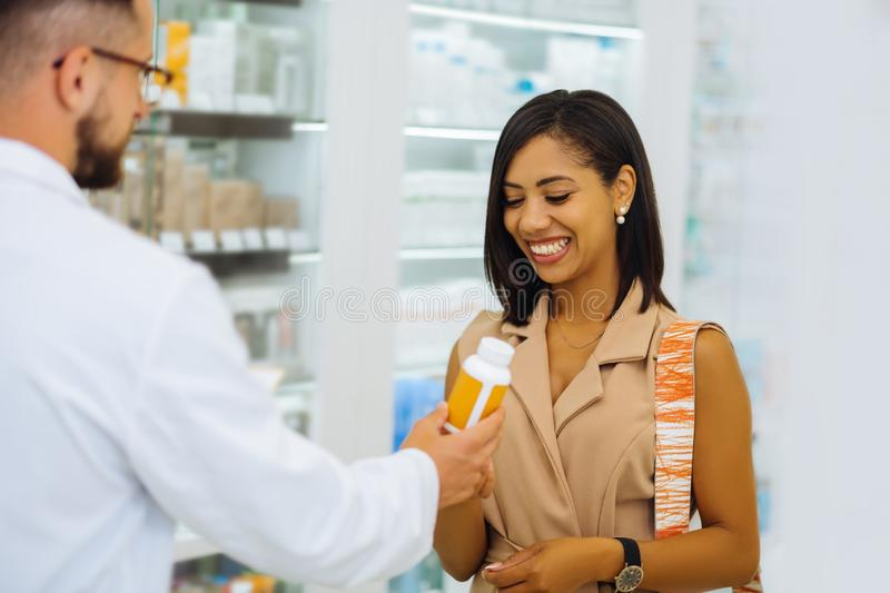 Cheerful dark-skinned client looking for skincare pills royalty free stock photo