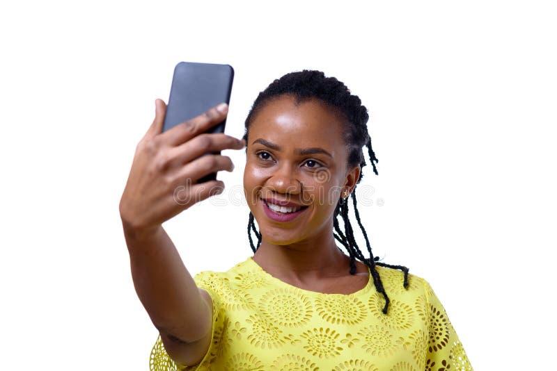 Smiling dark-skinned woman taking selfie. Cheerful dark-skinned woman taking selfie with smartphone against white background stock photo