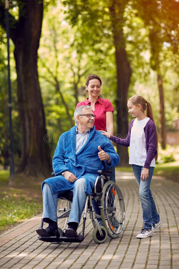 Cheerful daughter and grandchildren visiting disabled father in. Cheerful daughter and grandchildren visiting senior disabled father in park royalty free stock photo
