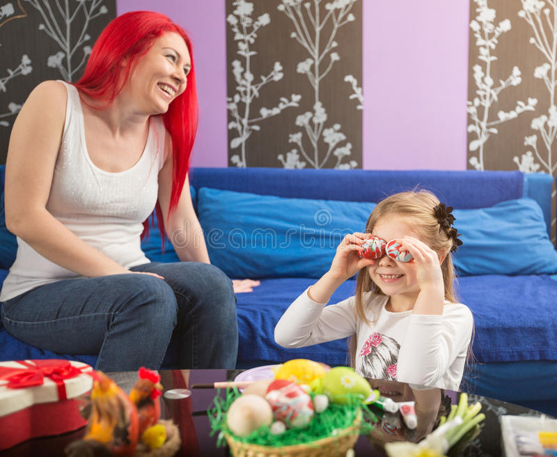 Cheerful daughter playful with Easter eggs stock image