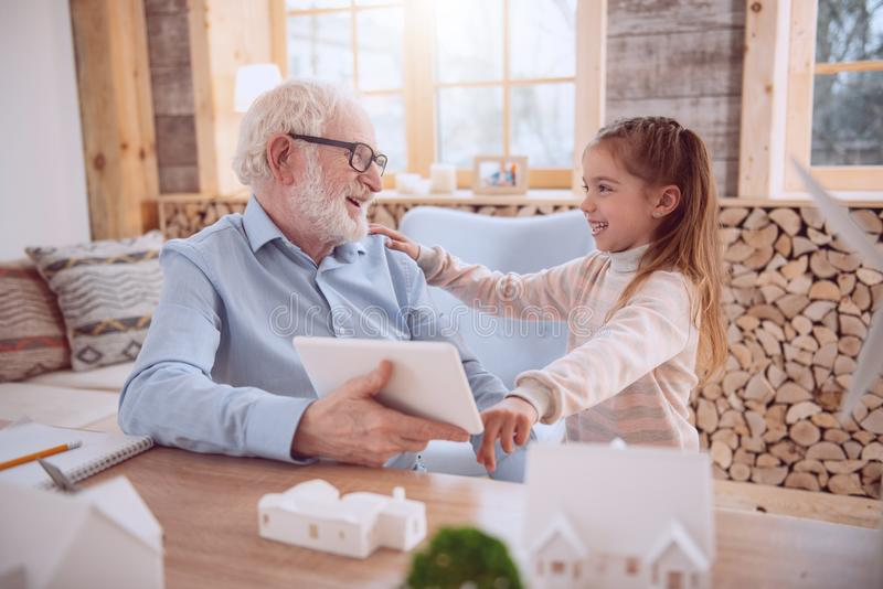 Cheerful delighted girl smiling to her grandfather royalty free stock image