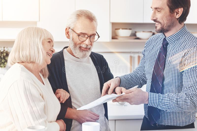 Cheerful delighted real estate agent talking with aged couple royalty free stock images