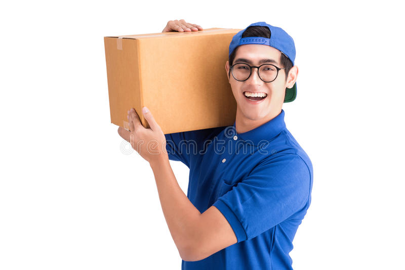 Cheerful delivery man. Happy young courier holding a cardboard box royalty free stock image