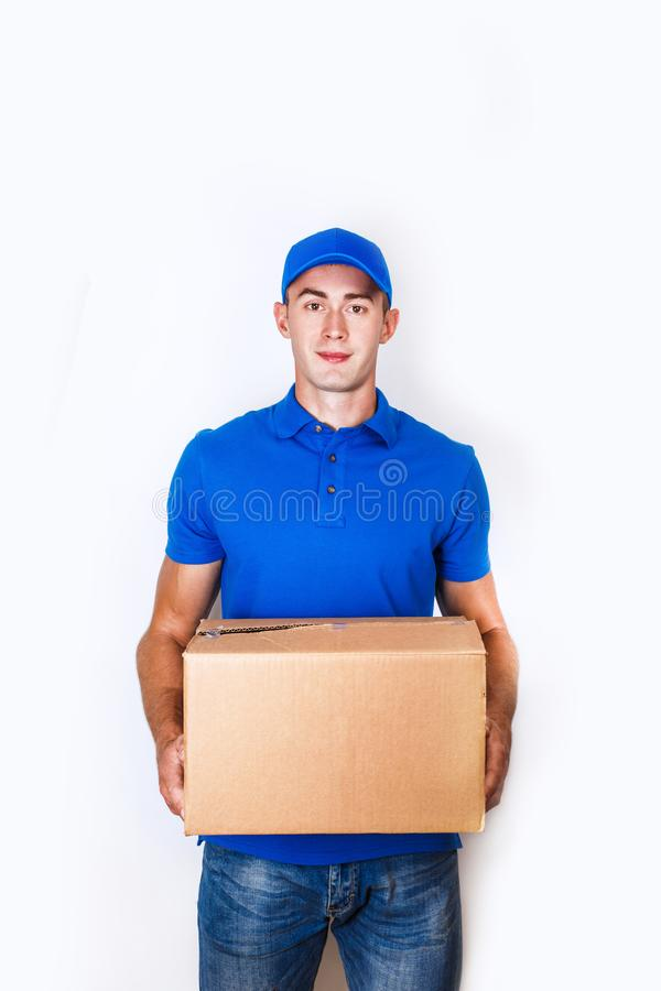 Cheerful delivery man. Happy young courier holding a cardboard box and smiling stock photos