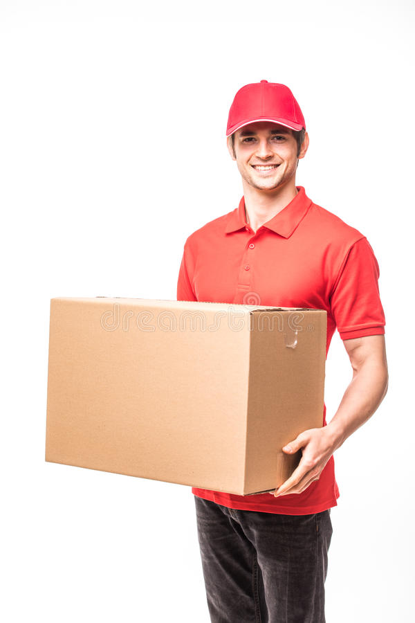 Cheerful delivery man happy young courier holding a cardboard box and smiling while standing on white background royalty free stock image