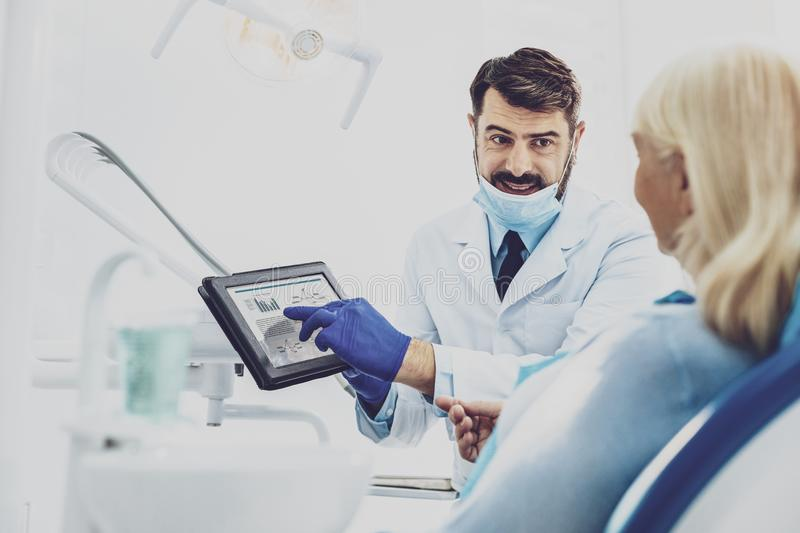 Cheerful dentist demonstrating his gadget. Scheme description. Delighted male person expressing positivity while looking at his patient royalty free stock photo