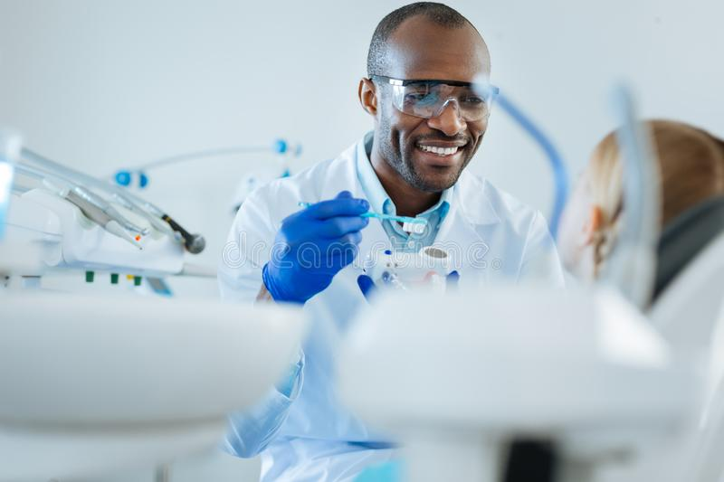 Cheerful dentist telling his patient about brushing teeth royalty free stock photography