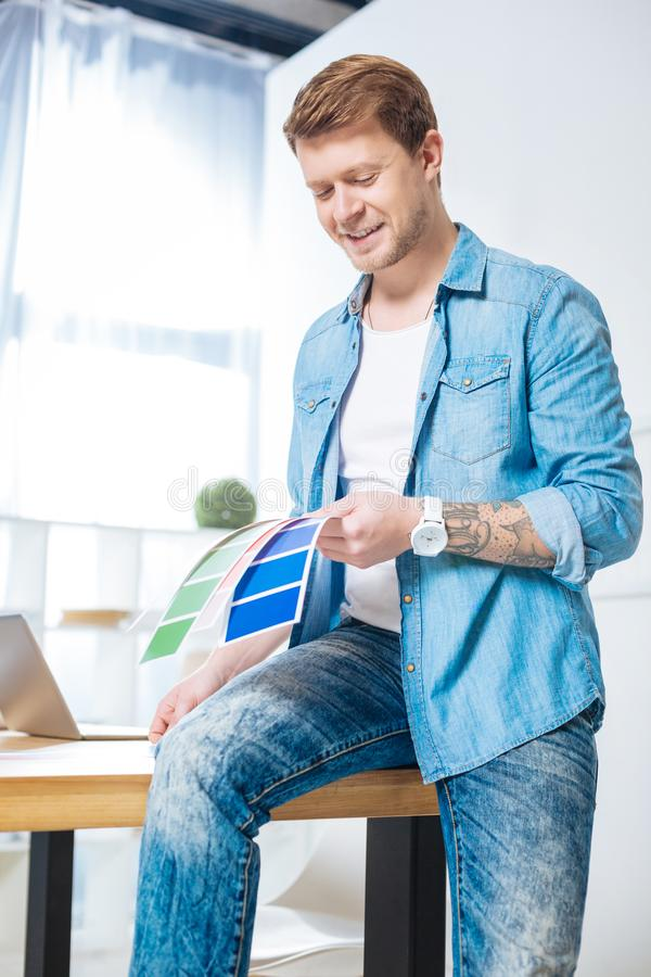 Cheerful designer feeling happy while holding color palettes. Perfect colors. Skilled experienced handsome designer smiling and feeling glad while sitting on the royalty free stock photos