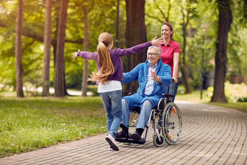 cheerful disabled grandfather in wheelchair welcoming his granddaughter. royalty free stock photo