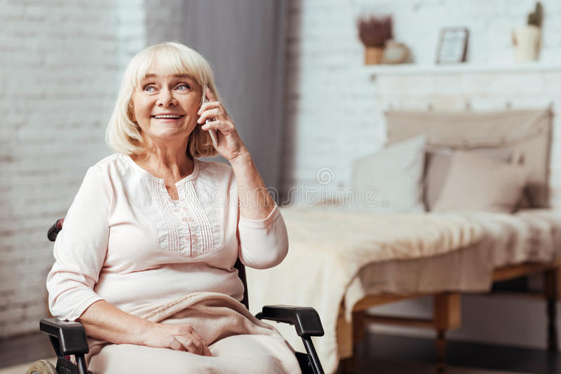 Cheerful disabled senior woman talkign on smart phone royalty free stock image
