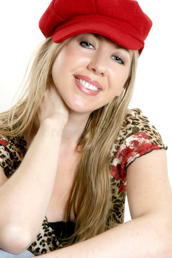 Cheerful disposition. Cheerful girl in relaxed pose. She has long blonde hair, is wearing a red cap and short sleeved patterned top stock photo