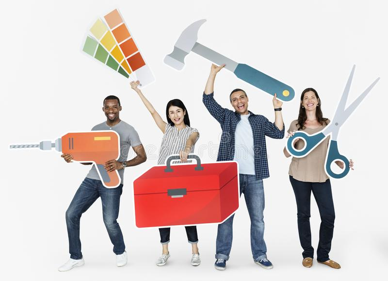 Cheerful diverse people holding tools royalty free stock photo