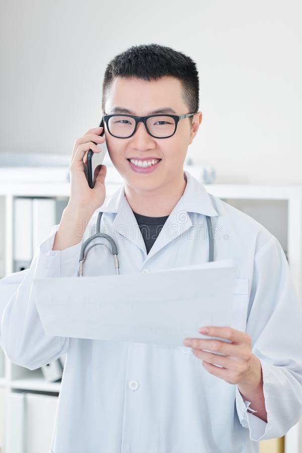 Cheerful doctor calling on phone stock photos