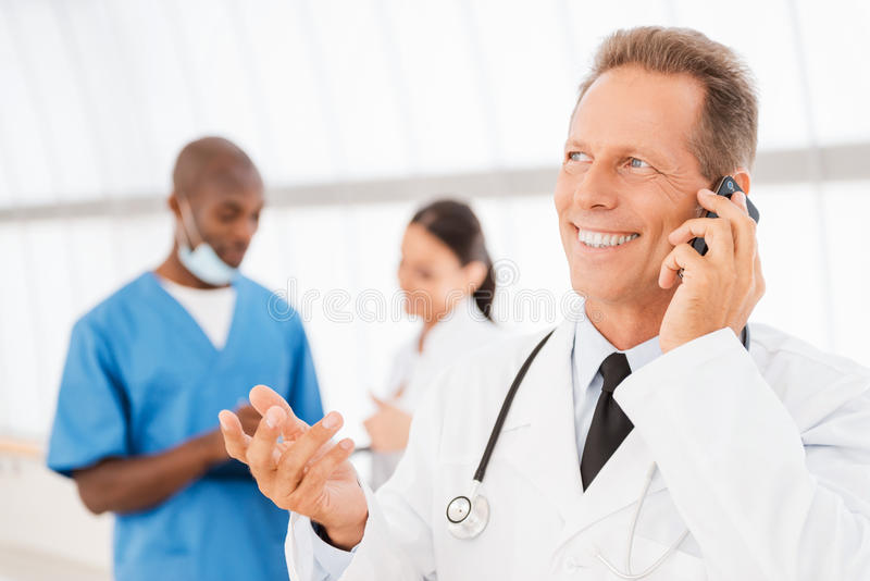 Cheerful doctor on the phone. Cheerful mature doctor talking on the mobile phone and gesturing while his colleagues talking in the background royalty free stock photos