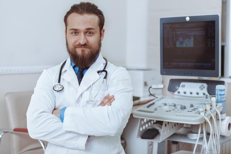 Cheerful doctor using ultrasound scanner at work. Confident male doctor posing roudly at his clinic near ultrasound scanner, copy space. Successful experienced royalty free stock image