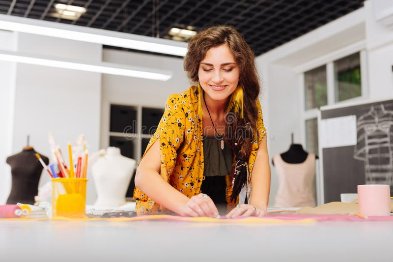 Cheerful dressmaker smiling while drawing lines on fabric stock photography
