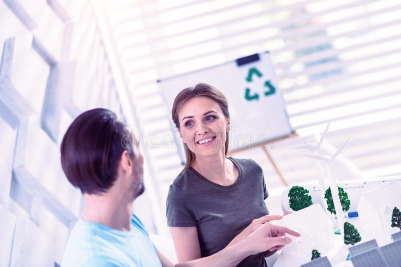 Cheerful eco engineer smiling to her client while working on his project royalty free stock photos