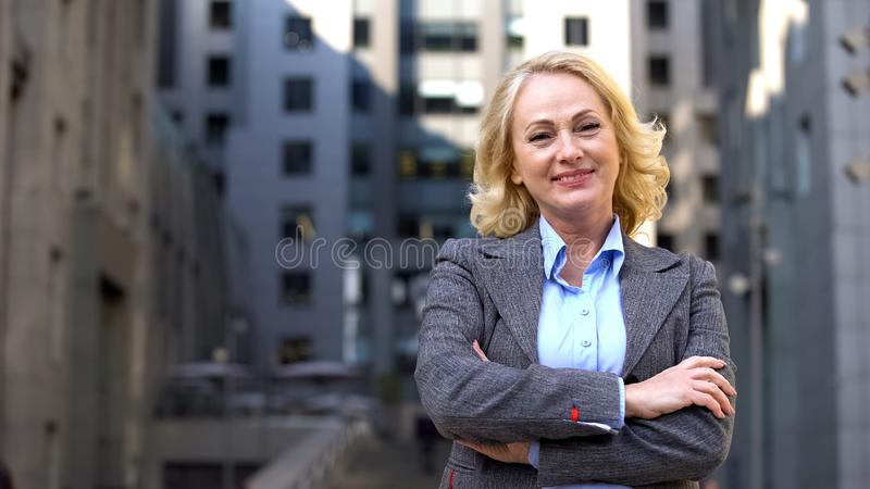 Cheerful elderly business woman looking camera outside office building, job stock image
