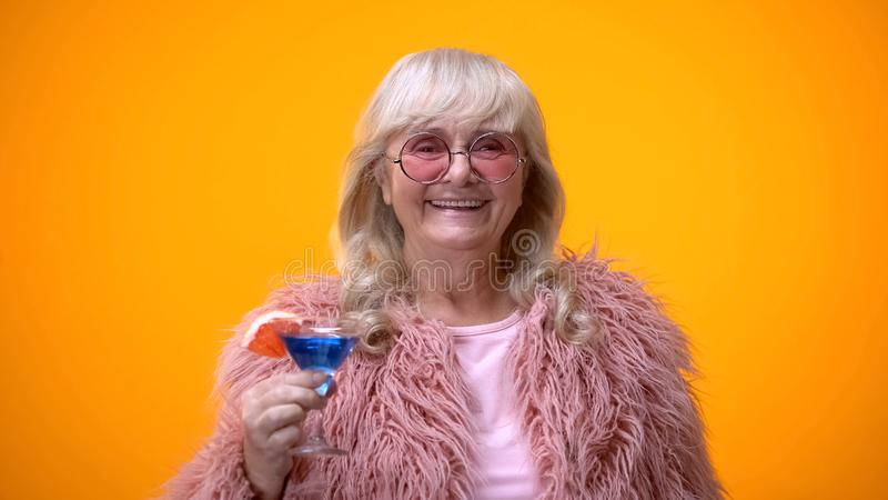 Cheerful elderly lady in funny pink outfit drinking blue cocktail, age positive stock images