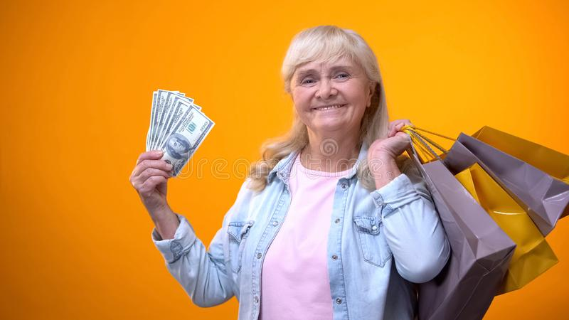 Cheerful elderly woman holding shopping bags and dollar cash, consumerism stock photography