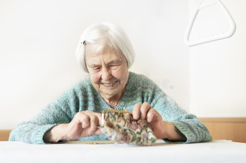 Cheerful elderly 96 years old woman sitting at table at home happy with her pension savings in her wallet after paying. Bills. Saving for retirement and royalty free stock photography