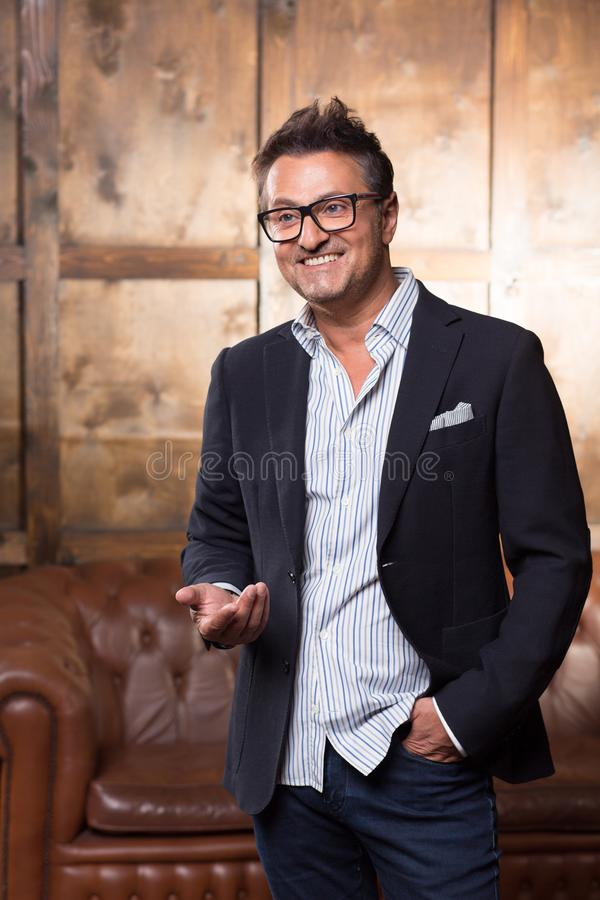 Cheerful elegant man standing alone and smiling happily stock photography