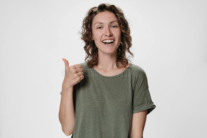 Cheerful enthusiastic pleased young caucasian curly woman showing thumbs up gesture royalty free stock photography
