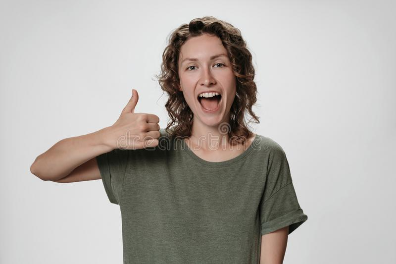 Cheerful enthusiastic young curly woman with opens eyes and mouth widely showing. Thumbs up gesture to camera, expression her like and approval of idea or stock photos