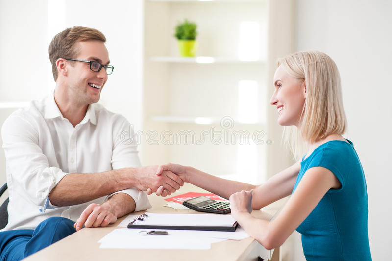 Cheerful estate agent and his female customer stock photo